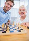 Father playing chess with his little boy. In the living room royalty free stock photo