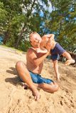 Father playing with child at beach royalty free stock images