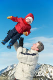 Father playing with child boy. Happy father playing with little child son boy in winter over mountain and blue sky Royalty Free Stock Photos
