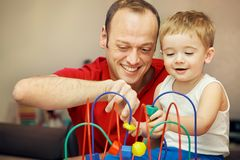 Father playing with child in developing game. Father playing with his child in developing game at home. Dad and son having fun Stock Photography