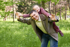 Father playing with child girl in summer park, sunlight, green grass and trees. Father playing with child girl in summer park, sunlight,  green grass and trees Stock Photo