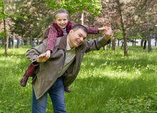 Father playing with child girl in summer park, sunlight, green grass and trees Royalty Free Stock Images