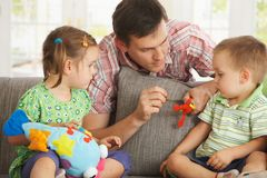 Father playing with children at home stock images