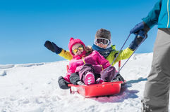 Father playing with children on snow Royalty Free Stock Image