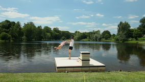 Father playing with daughter on floating platform on lake in France stock footage
