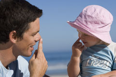 Father playing with daughter (2-3), touching noses with fingers, smiling, close-up, side view Royalty Free Stock Photo