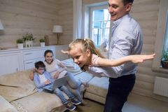 Father playing with daughter on weekend at home royalty free stock photo