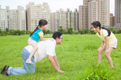 Father playing with daughters in the city park Stock Photography