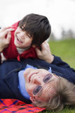 Father playing with disabled son. On grass at park Royalty Free Stock Images