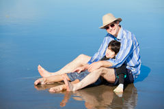 Father playing with disabled son on beach, holding him upright Royalty Free Stock Images