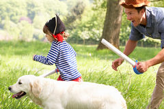 Father Playing Exciting Adventure Game With Son. And Dog In Summer Field Royalty Free Stock Image