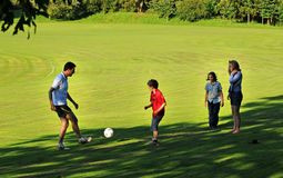 Father playing football with children. Outdoor family group playing football stock images