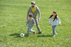 Father playing football with children on grass. In park stock photography