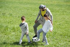 Father playing football with children on grass. In park royalty free stock photography