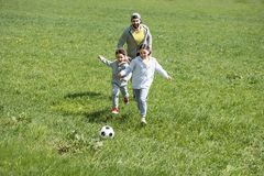 Father playing football with daughter and son. In park stock photography