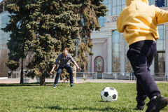 Father playing football with his little son outdoors in park. Image of bearded father playing football with his little son outdoors in the park. Looking aside stock photography