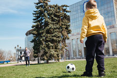 Father playing football with his little son outdoors in park. Picture of father playing football with his little son outdoors in the park stock photo