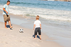 Father playing football with his son. At the beach Stock Images
