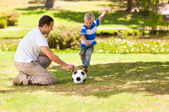 Father playing football with his son. Father and his son in the park Royalty Free Stock Photos