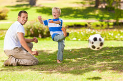 Father playing football with his son. In a park Stock Photography
