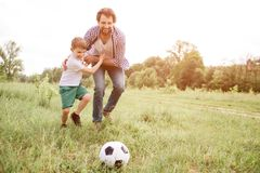 Father is playing football with his son. They are running down the meadow. Boy is hugging his dad and looking at ball. Man is doing the same thing Royalty Free Stock Photos