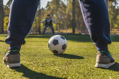 Father playing football with son. Ready to score a goal. Close-up of man legs standing near ball. Boy is standing at the gate with preparation stock photos