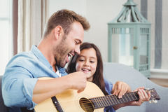 Father playing guitar with daughter Stock Image