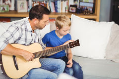Father playing guitar with son sitting on sofa Stock Photography