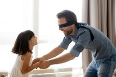 Father playing hide and seek with kid daughter at home. Happy blindfolded father playing hide and seek active game catching excited little kid daughter at home stock photos