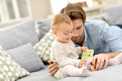 Father playing with his baby girl on sofa ta home Stock Photography