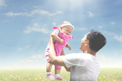 Father playing with his baby in the meadow Royalty Free Stock Photos