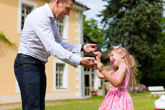 Father is playing with his daughter on a meadow. Family affairs - father and daughter playing in summer; he is dancing with her in the garden in front of the Royalty Free Stock Images