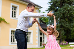 Father is playing with his daughter on a meadow. Family affairs - father and daughter playing in summer; he is dancing with her in the garden in front of the Stock Photography