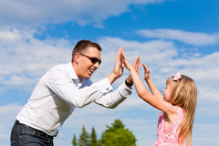 Father is playing with his daughter on a meadow. Family affairs - father and daughter playing in summer; he is dancing with her while having a walk Royalty Free Stock Image
