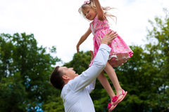 Father is playing with his daughter on a meadow. Family affairs - father and daughter playing in summer; he is throwing her into the air Stock Image