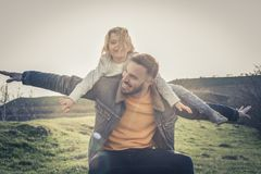 Father playing with his daughter in the park. Daughter lying on royalty free stock images