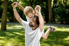 Father is playing with his little son. Father raised his little son on his right shoulder and smile. The boy is amazed. stock photo