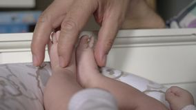 Father playing with his newborn daughters feet stock footage