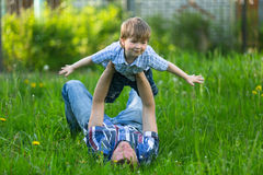 Father playing with his small son. In the grass royalty free stock image