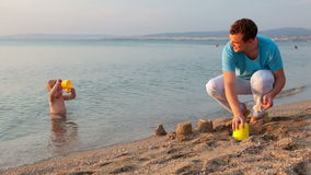 Father playing with his son at the beach stock footage