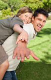 Father playing with his son in the park. Cute father playing with his son in the park Royalty Free Stock Photography