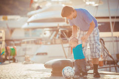 Father playing with his son on the pier near yacht club in summer. Outdoor. Young dad walking with a child on the waterfront near the yacht club on a warm sunny Royalty Free Stock Image