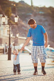 Father playing with his son on the pier near yacht club in summer. Outdoor. Young dad walking with a child on the waterfront near the yacht club on a warm sunny Royalty Free Stock Images