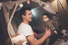 Father is playing with little baby daughter at night at home. royalty free stock image