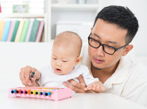 Father playing music instrument with baby. Asian family lifestyle at home. Father playing music instrument with baby. Sound development concept stock image