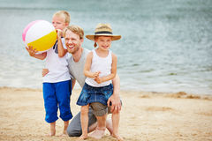 Father playing with siblings on beach in summer Royalty Free Stock Image