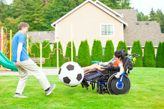 Father playing soccer with disabled son in wheelchai Stock Images