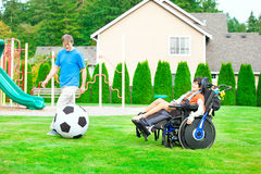 Father playing soccer with disabled son in wheelchai Royalty Free Stock Photo
