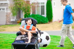 Father playing soccer with disabled son in wheelchai Royalty Free Stock Image