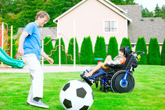 Father playing soccer with disabled son in wheelchair at park Stock Photography